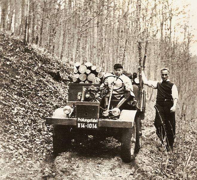 """Erste """"Prüffahrt"""", noch ohne Fahrerhaus, am 9. Oktober 1946. Chefkonstruk¬teur Heinrich Rößler am Steuer, rechts Hans Zabel, der Namensgeber des Unimog."""